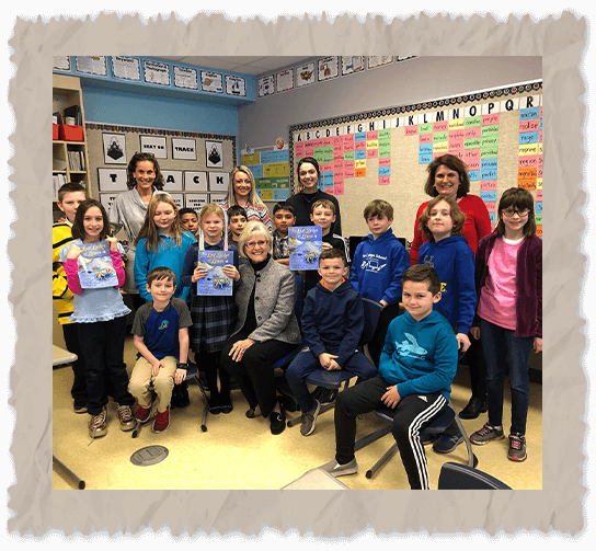Ilona E. Holland with kids in a classroom holding The Lost Locket of Lewes book